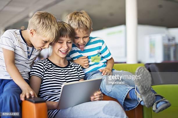 enfants en attente à l'aéroport de paris jouant avec une tablette - regarder vers le bas photos et images de collection