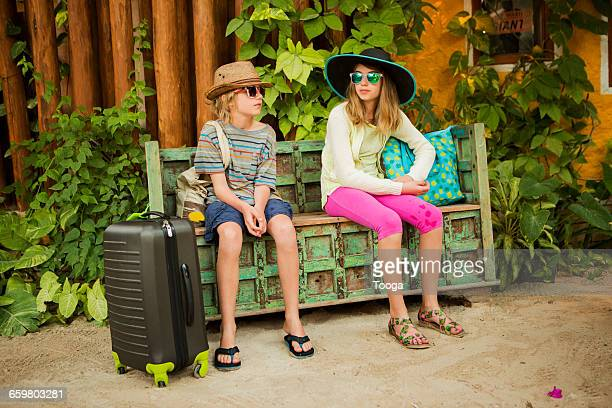 Kids waiting with suitcases