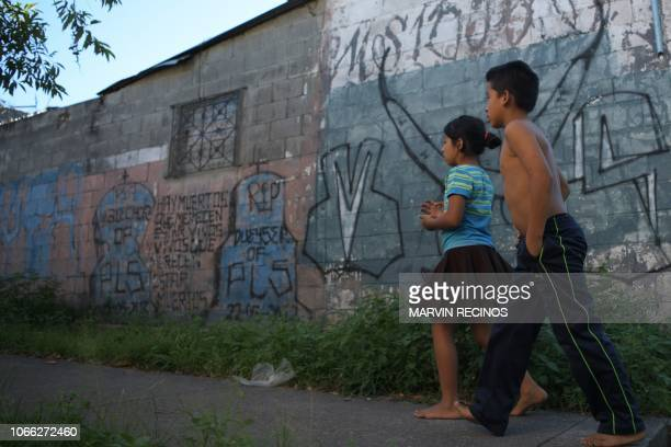 Kids walk by a graffiti representative of the MS-13 gang in the municipality of San Martin, El Salvador, on November 15, 2018. - The mayor of San...