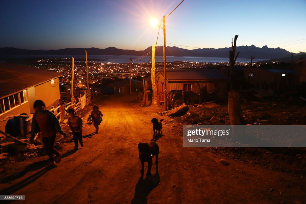 Kids walk past dogs in an informal mountainside community, whose residents depend on runoff water from the receding Martial Glacier, on November 5, 2017 in Ushuaia, Argentina. Many Ushuaians have constructed homes in informal settlements due to a population boom and lack of affordable housing available. Ushuaia is situated along the southern edge of Tierra del Fuego, in the Patagonia region, and is commonly known as the 'southernmost city in the world'. The city's main fresh water supply comes from the retreating Martial Glacier, which may be at risk of disappearing. In a 2015 report, warming temperatures led to the loss of 20 percent of the mass and surface of glaciers in Argentina over the previous 50 years, according to Argentina's Institute of Nivology, Glaciology and Environmental Sciences (IANIGLIA). Ushuaia and surrounding Tierra del Fuego face other environmental challenges including a population boom leading to housing challenges following an incentivized program attracting workers from around Argentina. Population in the region increased 11-fold between 1970 and 2015 to around 150,000. An influx of cruise ship tourists and crew, many on their way to Antarctica, has also led to increased waste and pollution in the area sometimes referred to as 'the end of the world'.