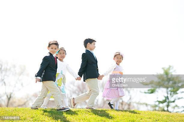 kids walking hand in hand - 一張羅 ストックフォトと画像