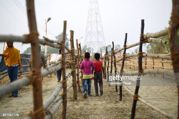 kids walking inside the fence during ganga sagar fair - ganga sagar stock photos and pictures