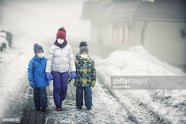 Kids walking on dirty snow wearing pollution mask.