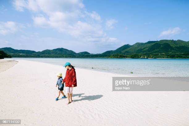Kids walking together on white sand beach on sunny winter day
