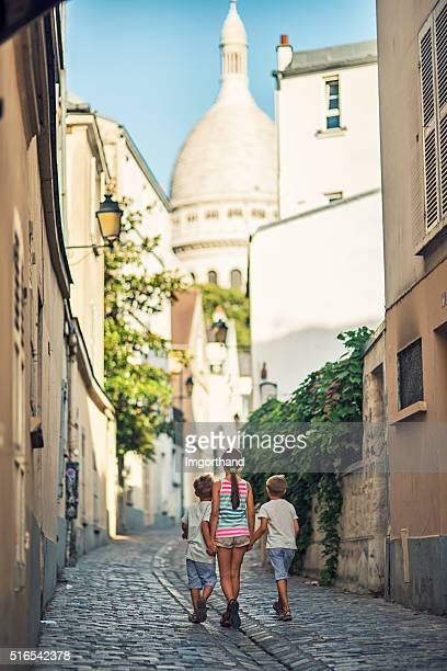 Kids walking towards Sacre Coeur in beautiful street of Montmartre