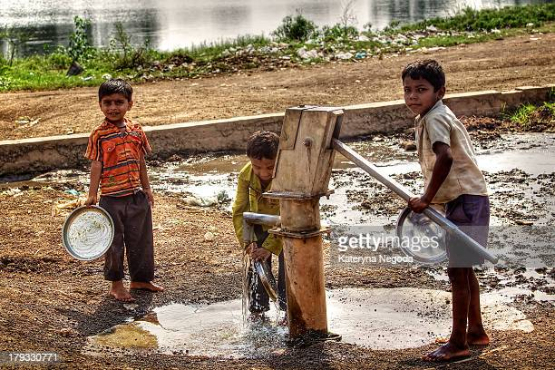 Kids washing their dishes using outdoor water standpipe after having lunch at school. Raipur, India.