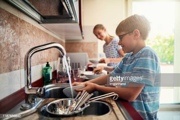 kids washing up dishes after lunch - chores stock pictures, royalty-free photos & images