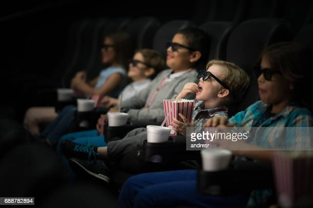 Kids watching a movie at the cinema wearing 3D glasses