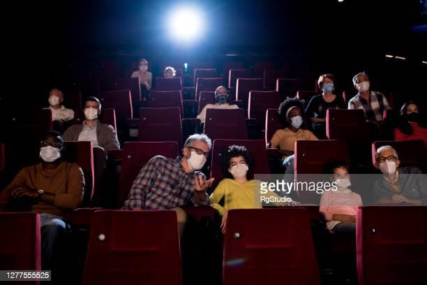 bambini che guardano un film con i nonni e indossano maschere per il viso al cinema - industria cinematografica foto e immagini stock