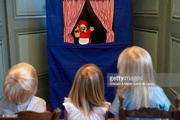 kids watching a puppet show - puppet show stock photos and pictures