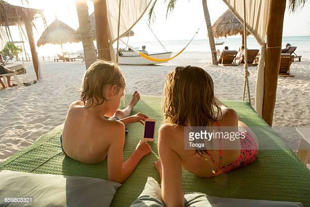 Kids watching smartphone at the beach
