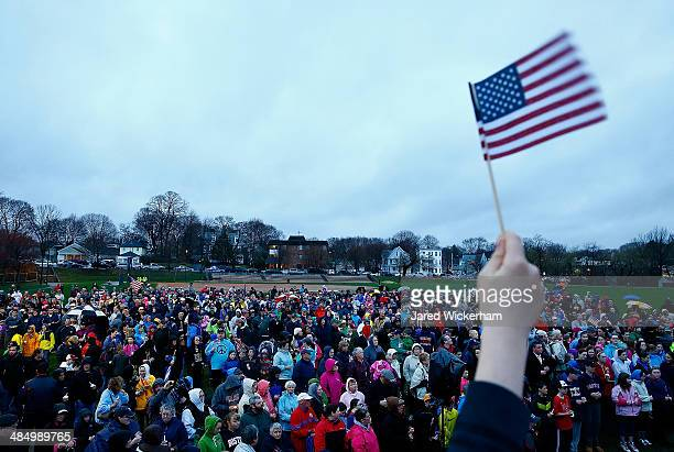 Kids wave their American flags at the start of a candlelight vigil for the oneyear anniversary of the Boston Marathon bombings at Garvey Park on...
