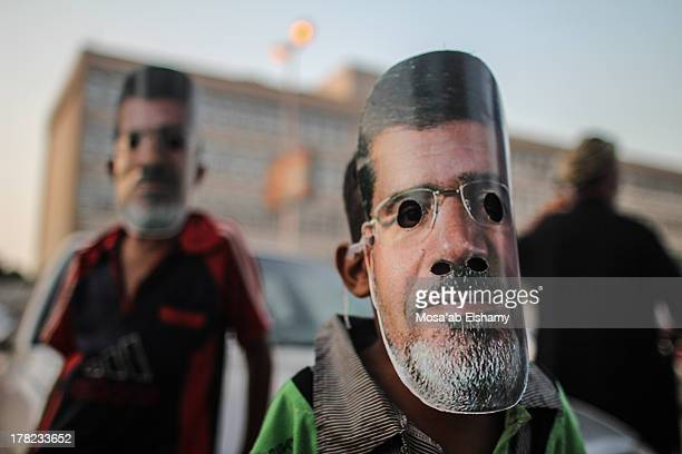 CONTENT] Kids wear masks depicting ousted president Mohamed Morsi in Rabaa Adaweya square where protesters have been camping calling for the return...
