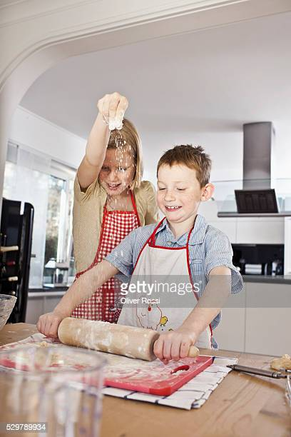Kids ( 5-6) wearing aprons and preparing dough in kitchen