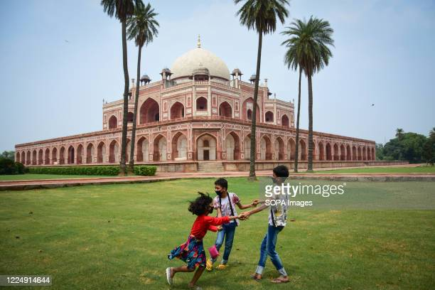 Kids wearing face masks as a preventive measure play in front of Humayun's Tomb. Humayun's Tomb reopened its doors for visitors after a three-month...
