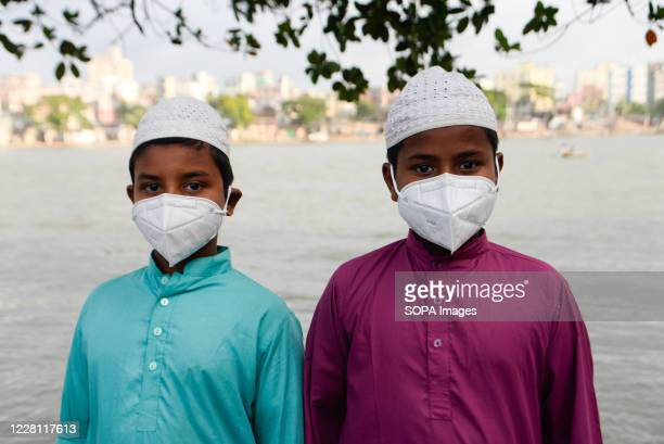 Kids wearing face masks posing for a picture close to Buriganga River. Dhaka is getting back to its normal life after some months of the ongoing...