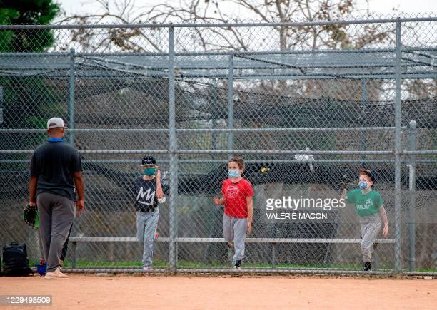 Kids wearing facemasks attend baseball practice at Pan Pacific Park amid the coronavirus pandemic, November 6 in Los Angeles, California.