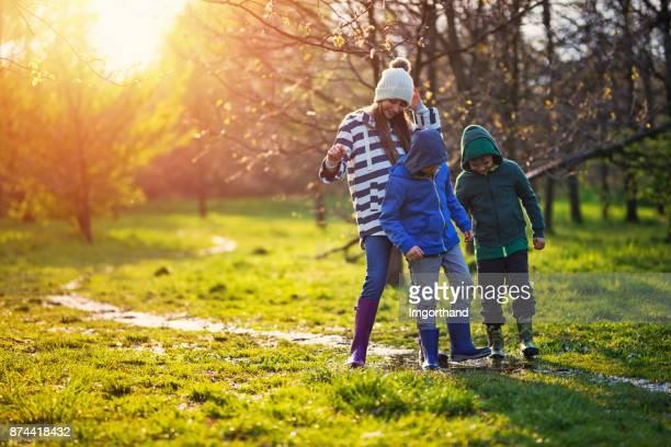 Kids wearing galoshes enjoying muddy path