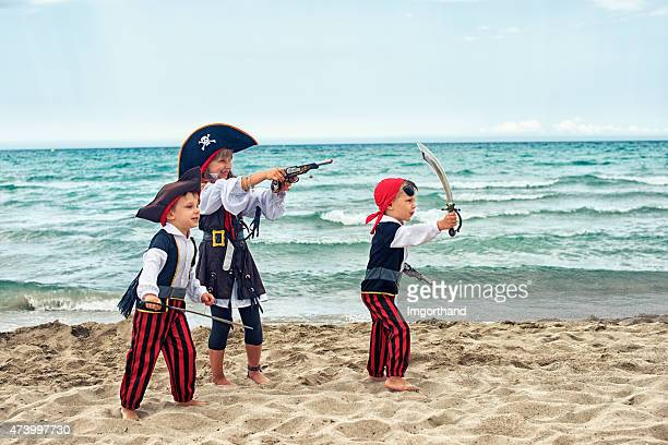 Kids wearing pirate costumes playing on the beach.