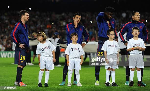 Kids wearing 'Unite against Racism' tshirt to highlight UEFA's FARE Action Week campaign stand with Lionel Messi Alexis Sanchez and Javier Mascherano...
