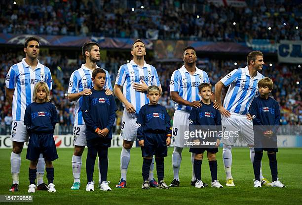 Kids wearing 'Unite against Racism' tshirts to highlight UEFA's FARE Action Week campaign stand with Malaga CF players during the UEFA Champions...