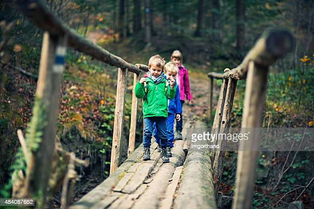 Kids with backpacks hiking in autumn forest