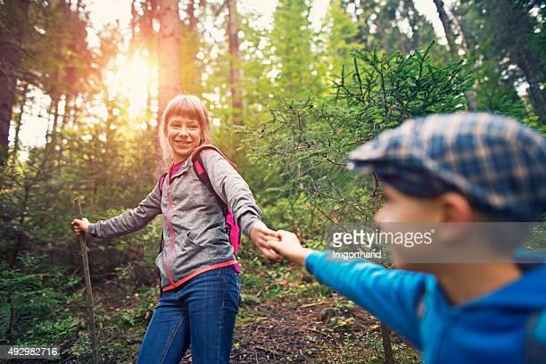 Enfants avec sacs à dos de randonnée en forêt