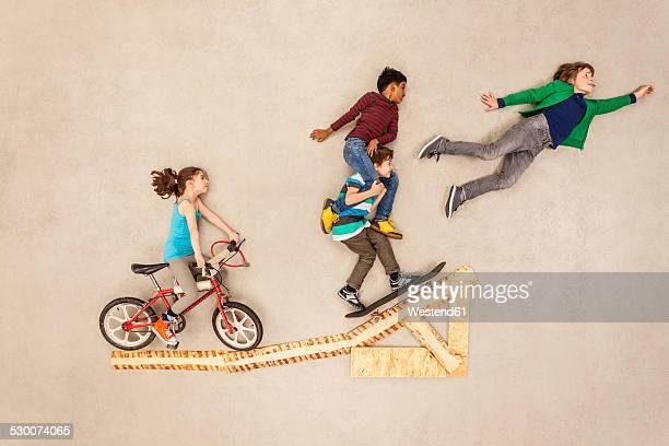 Kids with bike and skateboard on jump