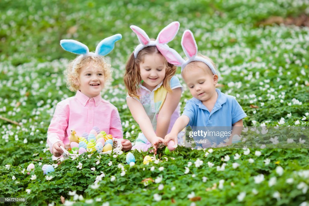 Kids with bunny ears on Easter egg hunt. : Stock Photo