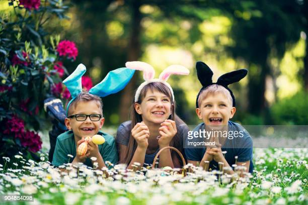 Kids with bunny ears playing easter egg hunt in garden