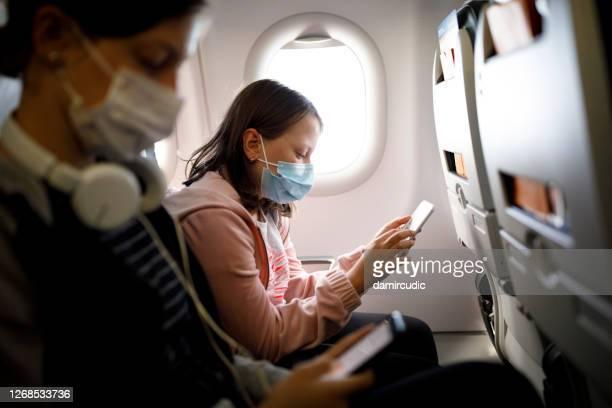 barn med ansiktsskyddande mask med mobiltelefon i flygplan - luftfarkost bildbanksfoton och bilder