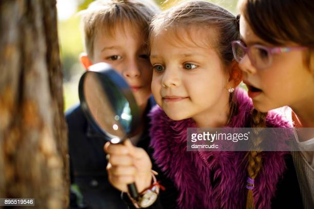 kids with magnifying glass - curiosity stock photos and pictures