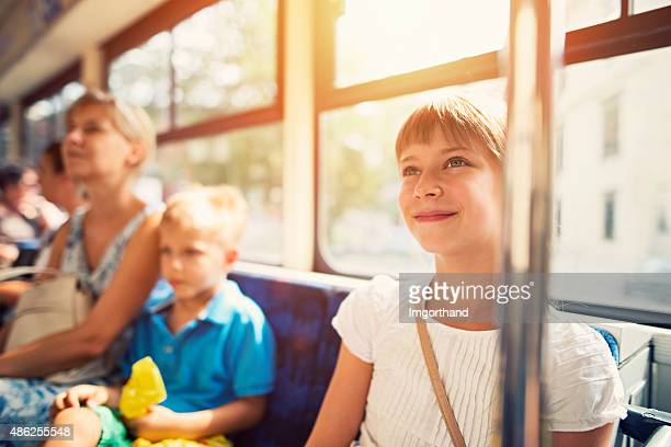 kids with mother travelling by public transport bus - tram stockfoto's en -beelden