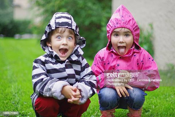 kids with rain coats having fun under the rain - under tongue stock pictures, royalty-free photos & images
