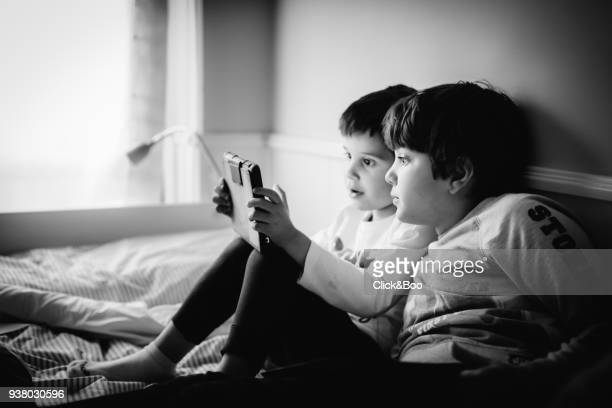 Kids with tablet on a bed