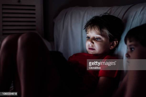 Kids with tablet on a sofa with soft light