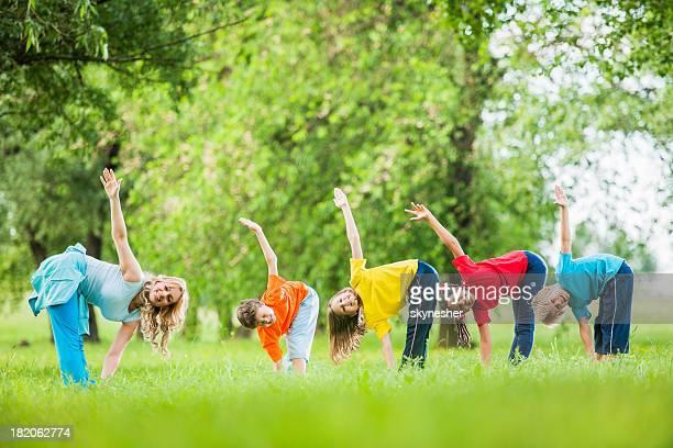 Los niños con sus PE maestro hacer ejercicios al aire libre.