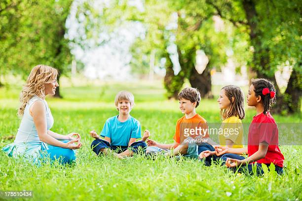 Kids with their yoga instructor exercising.