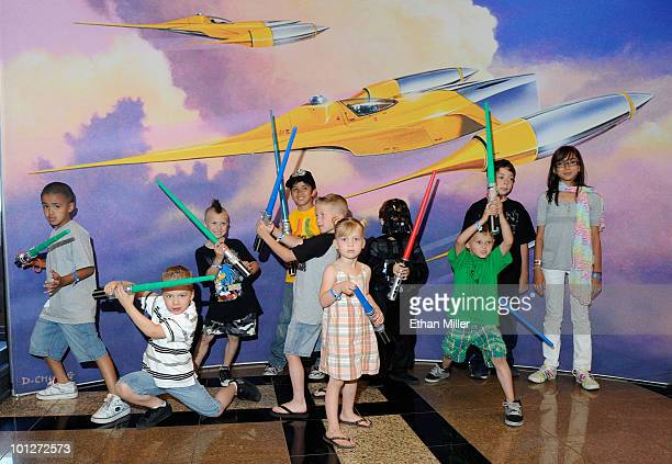 Kids with toy lightsabers pose in front of Star Wars artwork at the museum exhibit of 'Star Wars In Concert' at the Orleans Arena May 29 2010 in Las...