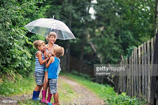 Kids with umbrella enjoying rain.