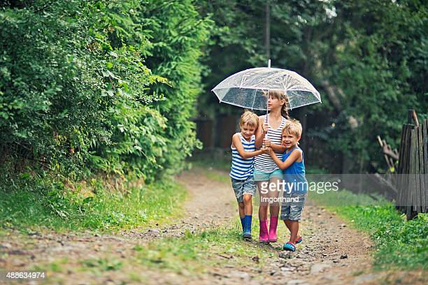 Kids with umbrella walking in the rain.