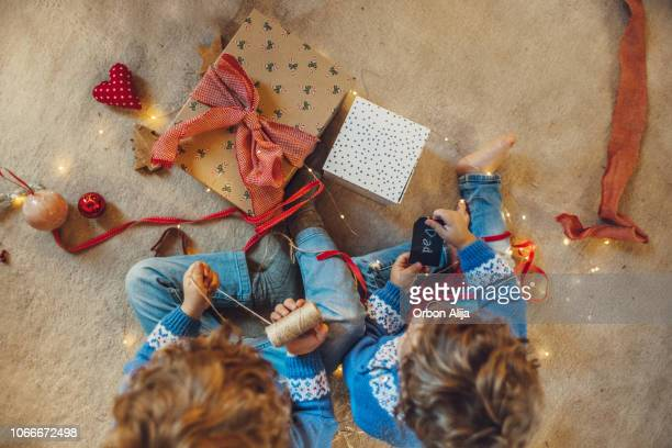 kids wrapping christmas gifts - christmas gifts stock photos and pictures