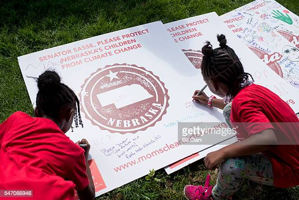 Kids write their names and decorate signs calling on senators to act on climate change legislation during the Moms Clean Air Force playin for climate...