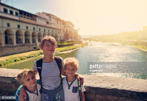 Kidss tourist posing at the famous Ponte Vecchio in Florence, Italy