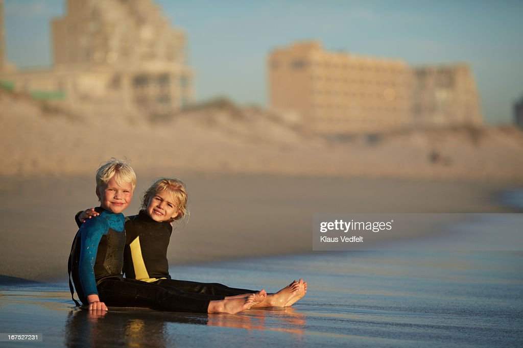 2 kidt sitting together on beach : Stock Photo