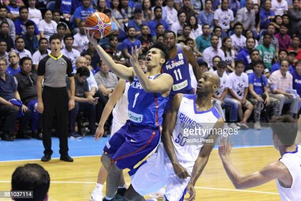 Kiefer Isaac Ravena of the Philippines drives past two players from soars past Quincy Davis III of Chinese Taipei to convert an uncontested layup...