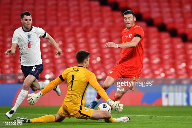 Kieffer Moore of Wales collides with Nick Pope of England as Michael Keane of England looks on during the international friendly match between...