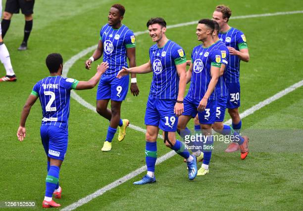 Kieffer Moore of Wigan Athletic celebrates with his team mates after scoring his team's fifth goal during the Sky Bet Championship match between...