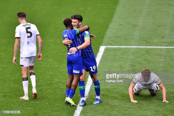 Kieffer Moore of Wigan Athletic celebrates with Jamal Lowe after scoring his team's fifth goal during the Sky Bet Championship match between Wigan...