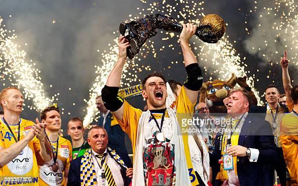 Kielce's Julen Aguinagalde celebrates with the trophy and teammates after winning the Handball EHF Champions League final Four Final match between KS...
